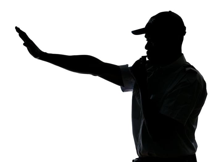 Traffic cop making stop gesture.