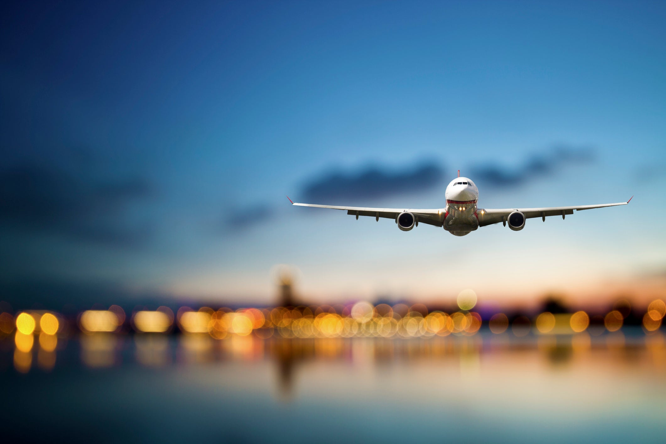 Commercial aircraft in flight with cityscape background