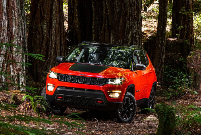 A red 2018 Jeep Compass Trailhawk, a compact SUV, in a forest.