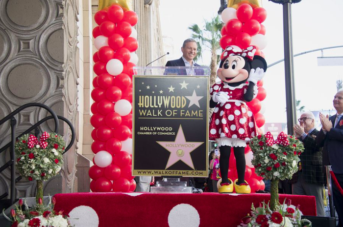 Disney CEO Bob Iger and Minnie Mouse stand on stage to accept a Hollywood Walk of Fame star
