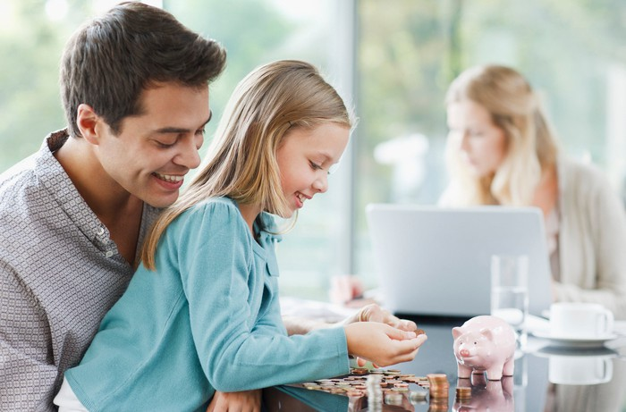 A smiling man watches a girl with a piggy bank and stacks of coins.