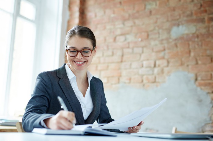 Smiling professional young female writing in a notebook