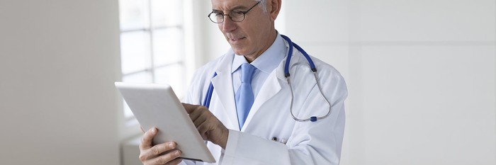 A doctor works on a tablet computer.