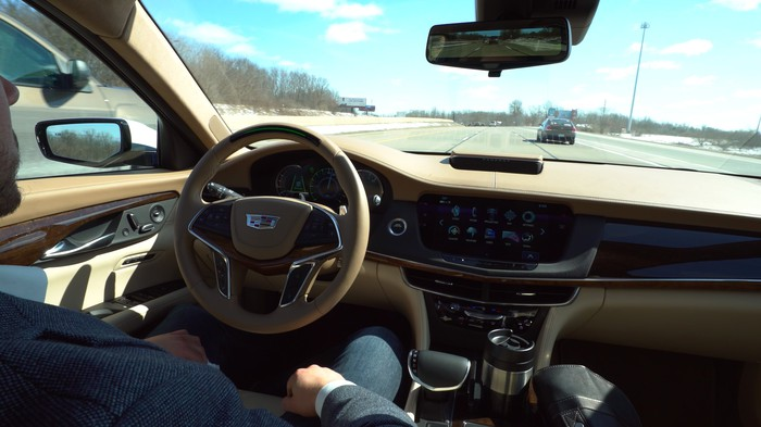 A view of the dashboard of a Cadillac CT6 that is cruising on the highway, showing the special steering wheel that is part of the Super Cruise system. The driver's hands aren't on the wheel.