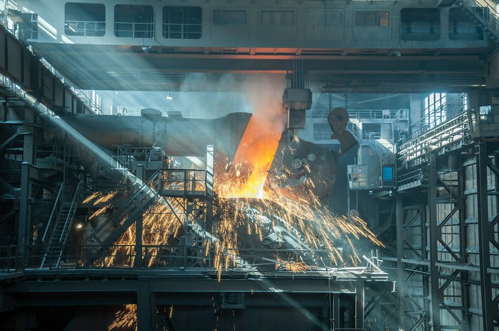 The inside of a steel factory with sparks flying out of a furnace.