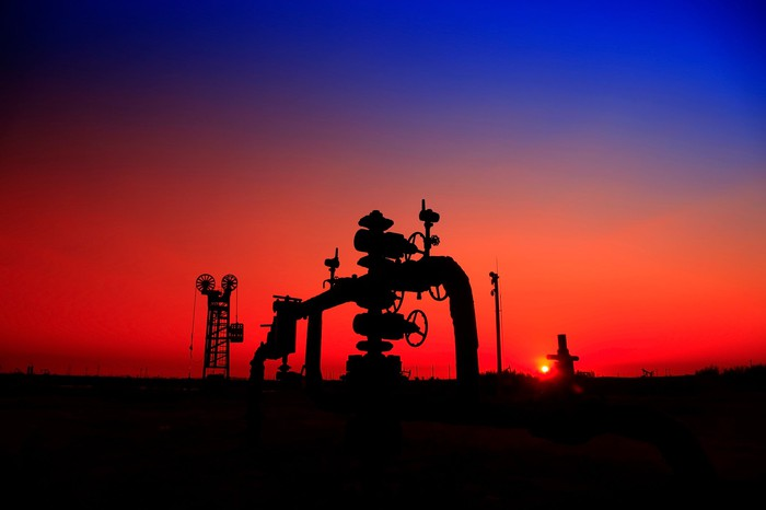A natural gas well with pipelines at sunset.