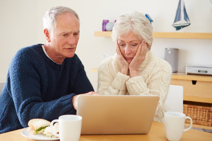 A visibly worried elderly couple reading a news article on their laptop.