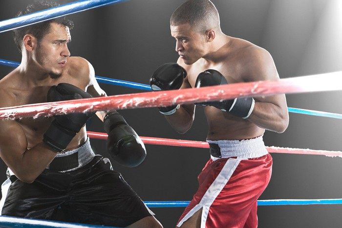 Two boxers squaring off in a boxing ring.