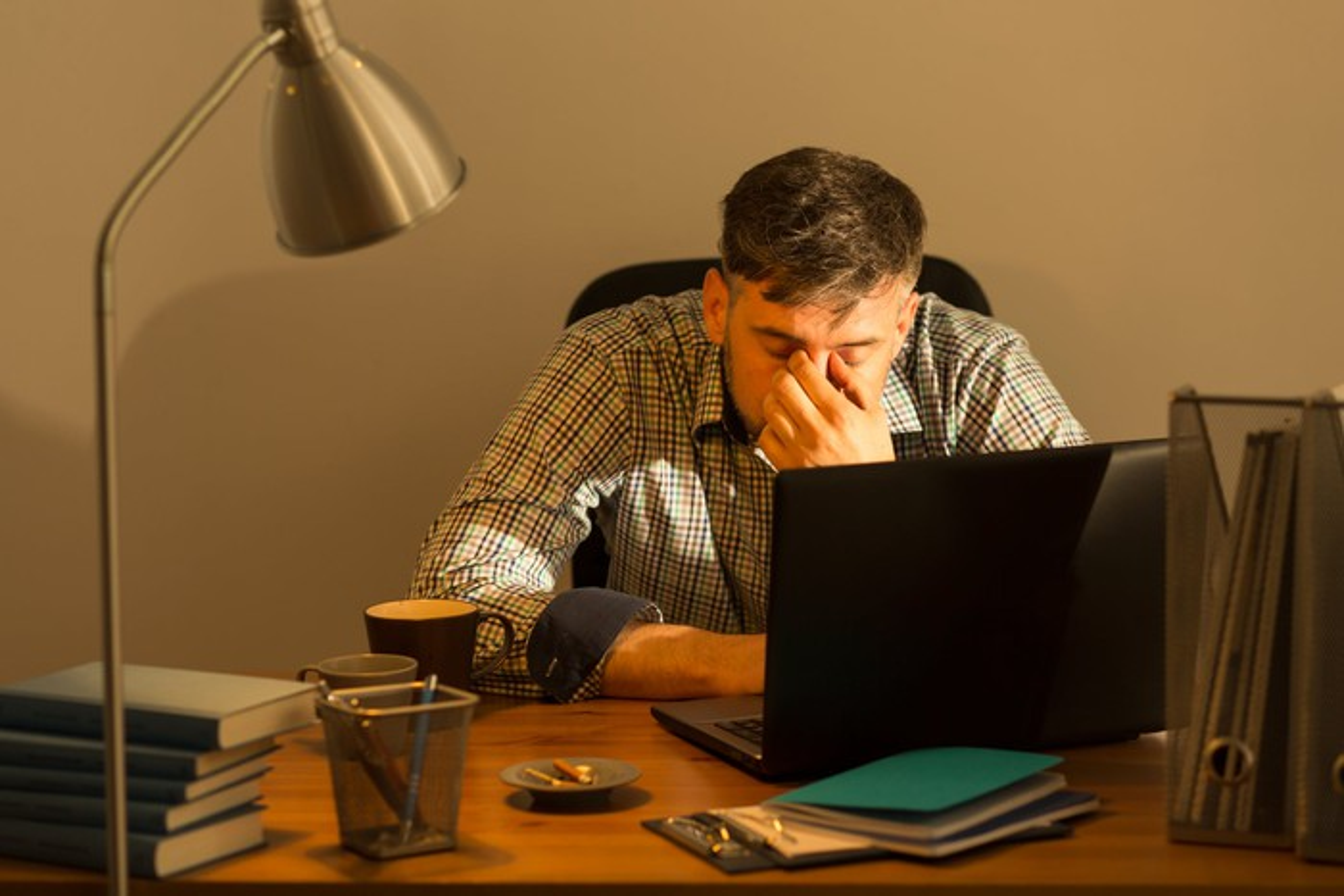 Man at a laptop rubbing his eyes
