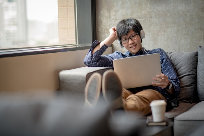 Young Asian man relaxing on a couch with his laptop and headphones.