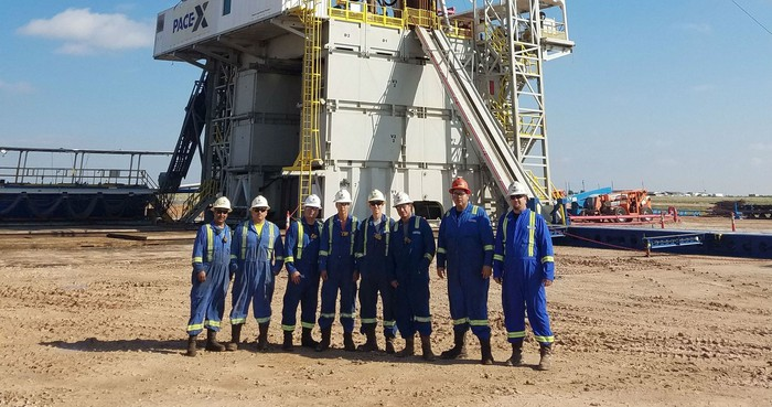 Eight workers wearing hardhats in front of a drilling rig on sandy ground under a clear blue sky.