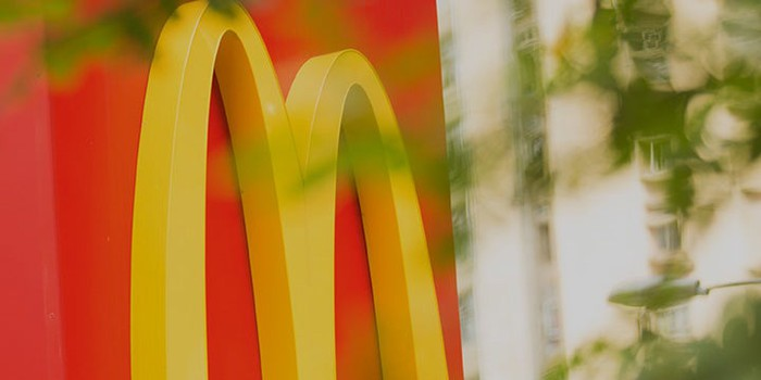 Detail of McDonald's red and yellow signage behind leafy, blurred foreground.