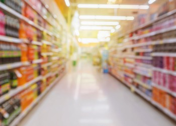 Blurred View of Supermarket Aisle With Soft Drink Bottles