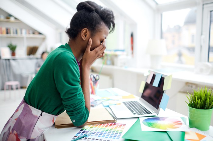 Woman with her face in her hands in front of a computer with numerous sticky notes and color palettes littered all over the desk.