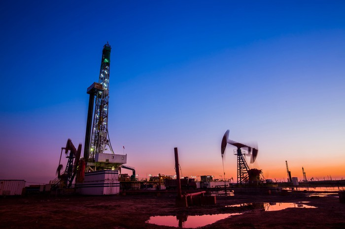 Drilling rig next to several pumpjacks at sunset.