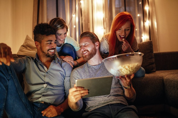 Friends sitting on a couch and on the floor. One holds a tablet and a bowl of popcorn.