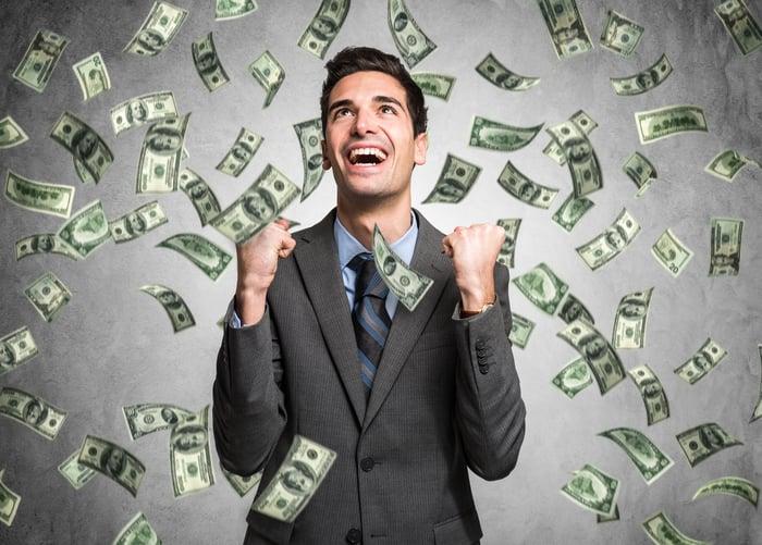 A man smiling while cash flies around him.