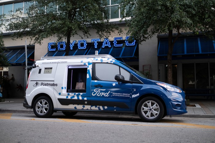 A modified Ford Transit Connect van is parked outside of a taco restaurant in Miami, Florida.