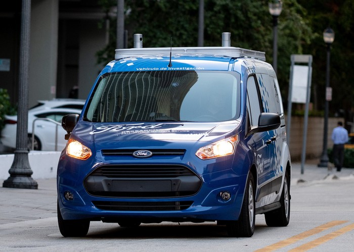 The modified Ford Transit Connect is shown from the front, with what appear to be self-driving sensors visible on the roof.
