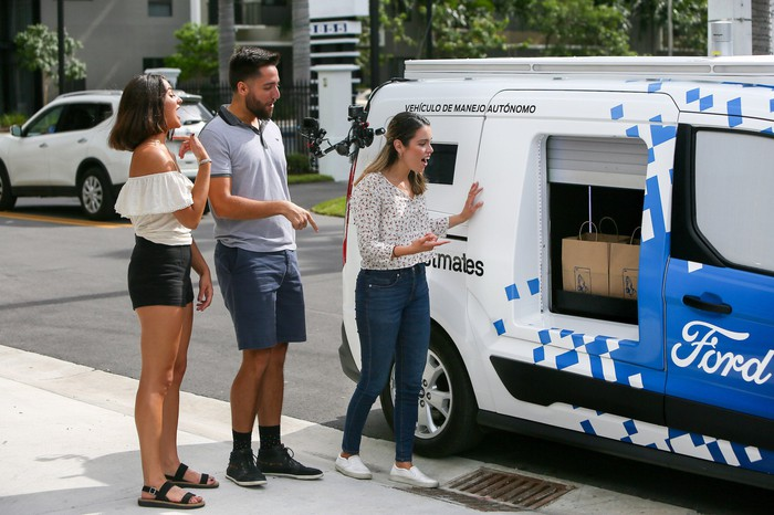 The modified Ford Transit Connect is shown parked at a curb with one of its lockers open, and three people are waiting to take the contents.