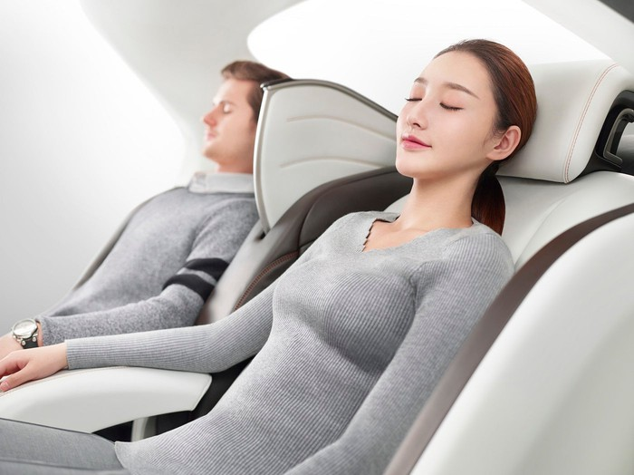 Two people with eyes closed leaning back in luxurious custom seats.