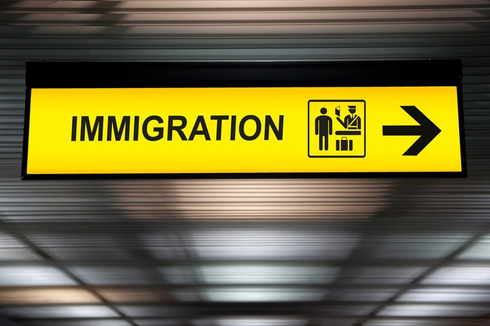 Yellow sign at airport that points to the right and says Immigration