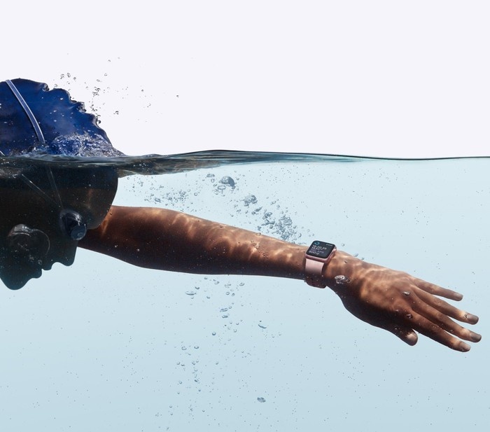 A person in a swim cap and goggles swimming while wearing an Apple Watch.