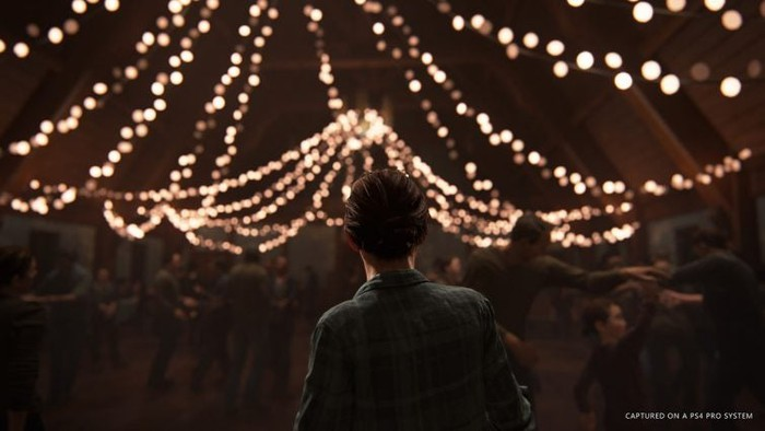 Ellie from Sony's The Last of Us 2 looking at decorative lights inside of a barn.