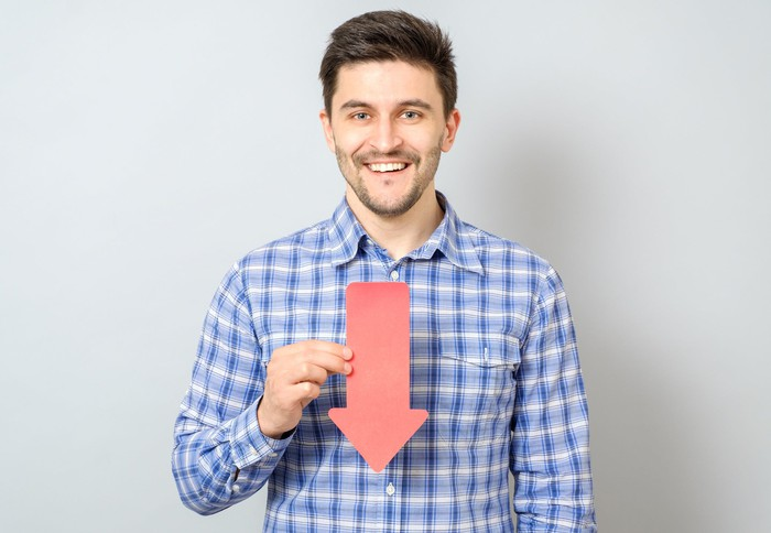 Man smiling while holding arrow that's pointing down
