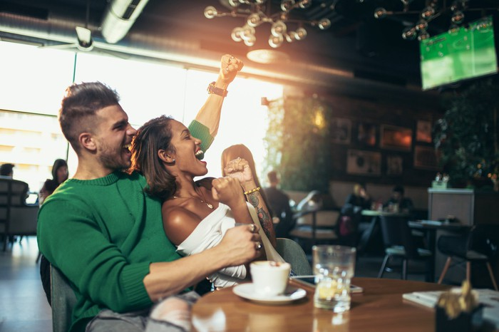A couple cheering while watching a game on television in a sports bar