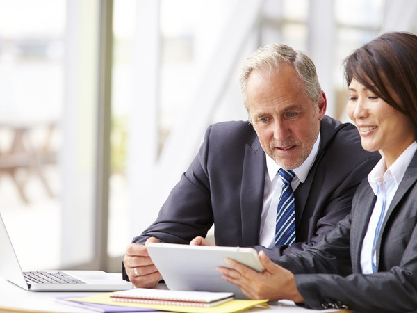older man in business suit reviewing document with woman in business suit_GettyImages-487810888
