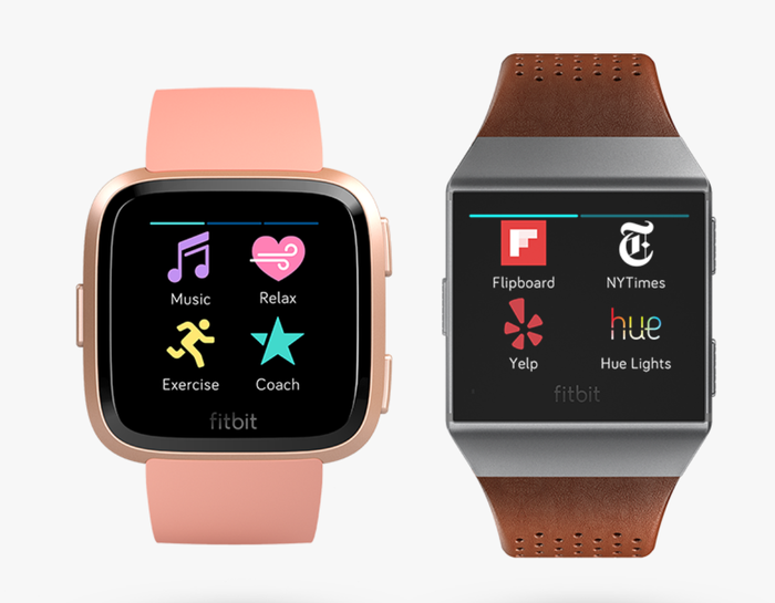The Fitbit Versa, with rounded edges and in pink, displayed on the left. On the right is the older Ionic, with square edges, silver trim, and brown leather band.