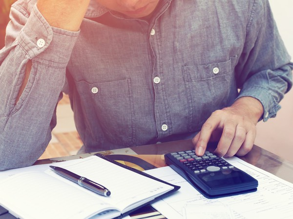 man using calculator_saving enough for retirement_GettyImages-639425630