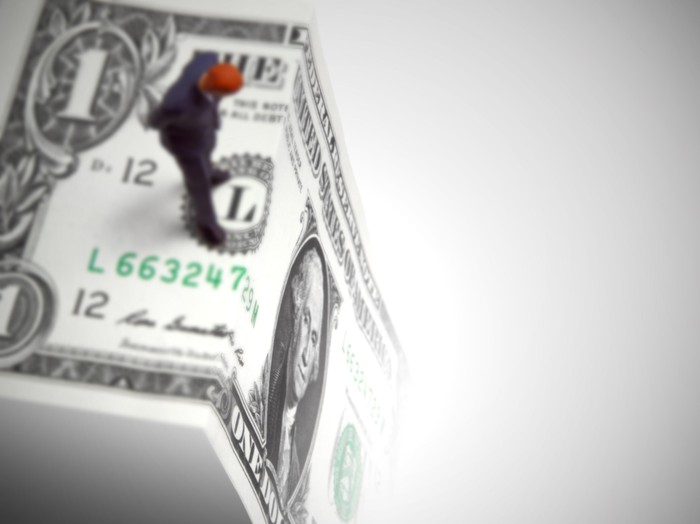 Man standing on edge of folded $1 bill