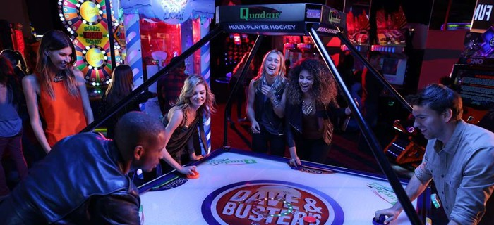 a group of young people playing a type of air hockey at a Dave & Buster's.
