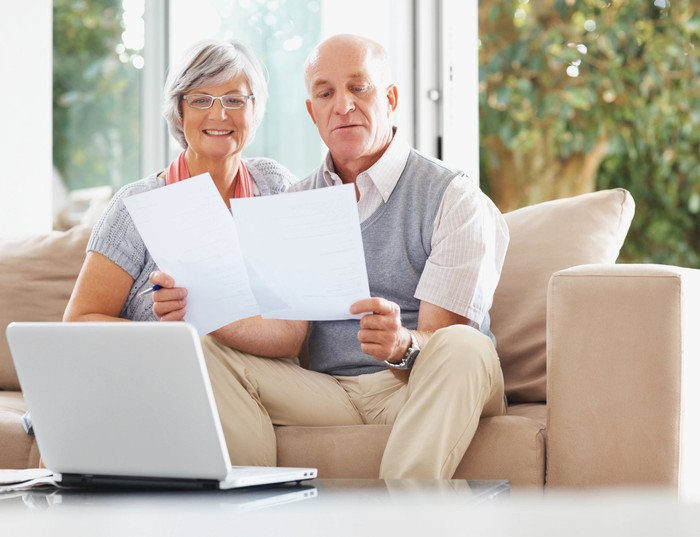 Older couple reviewing documents on a couch