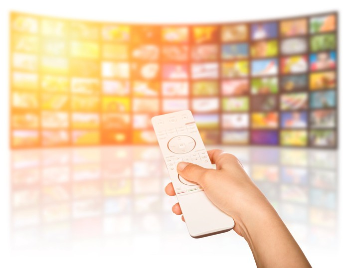 A person pointing a remote at a collection of screens displaying different images.