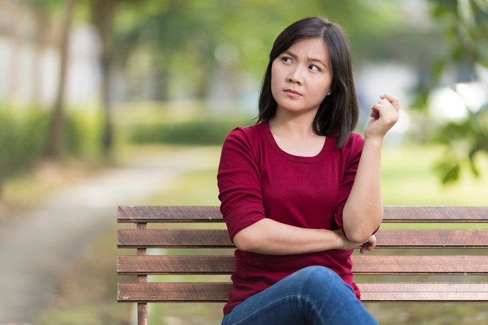 A woman sits on a park bench looking puzzled about something