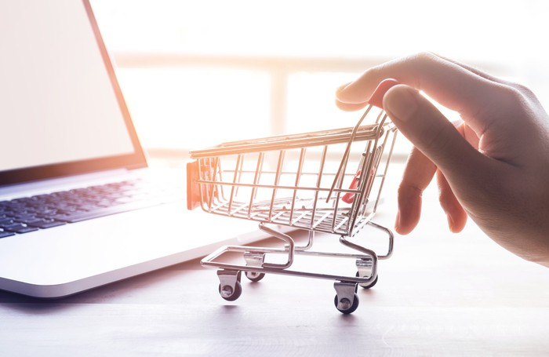 A hand pushing a miniature shopping cart next to a laptop.