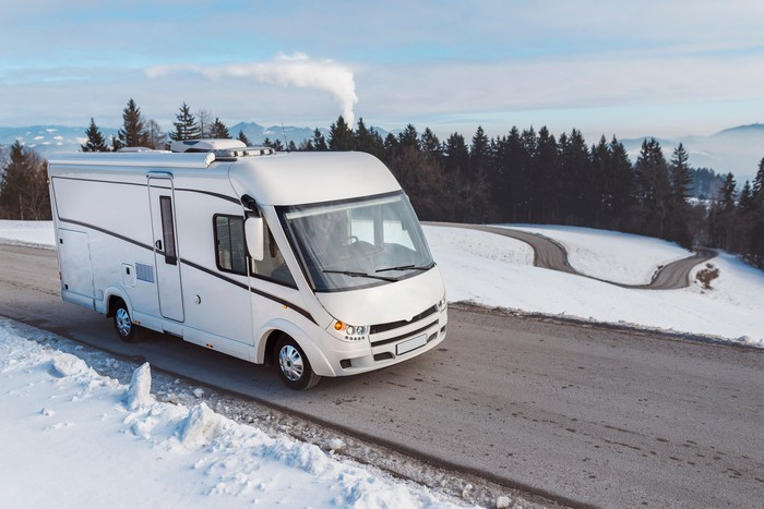 An RV driving on a road winding up a snowy hill, with pine trees in the background