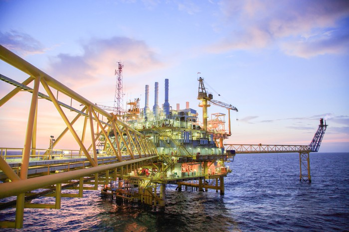 Offshore oil platform at sunset.