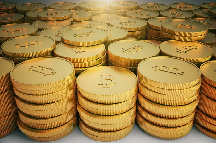Stacks of gold coins with bitcoin symbols.
