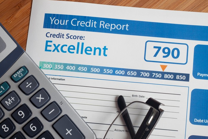 A credit report with an excellent score laid on a table next to a calculator and a pair of reading glasses.