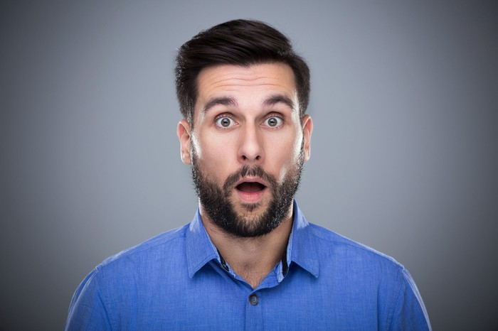 A man with a beard looks into the camera with a surprised open-mouth expression.
