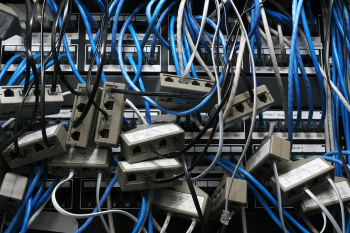 A rack of networking routers and switches, populated by a jumble of blue Ethernet cables and random adapters.