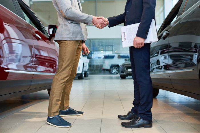 A customer shaking hands with a car salesman standing between two cars in a showroom.