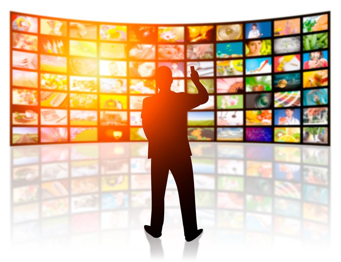 Silhouette of a man holding a remote, standing in front of many screens