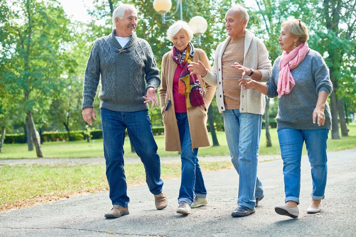 Group of four older people walking.