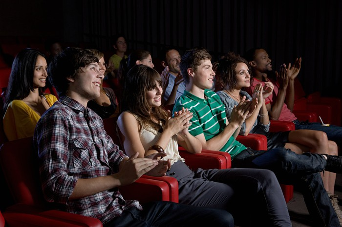 A movie theater full of smiling and clapping viewers.
