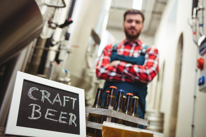 Craft brewer standing behind an 8-pack of beer, next to a small chalkboard reading CRAFT BEER